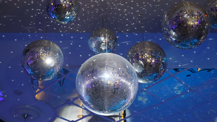 Several sparkling disco balls spinning with flashing lights during music band performance or dancing party. Party lights disco balls on blue background. Disco ball with bright rays, 4 k video Royalty-Free Stock Footage #1058539249