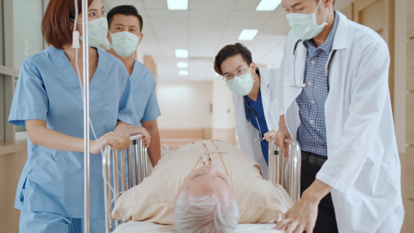 Group of Asian emergency doctor and nurse team wear face mask, push emergency stretcher, transport senior patient in hospital. Health care paramedic service, or medical rescue team operation concept Royalty-Free Stock Footage #1058540935