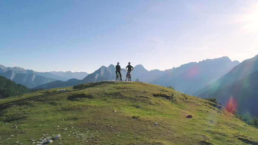 Aerial - Flying around two mountain bikers enjoying the view on top of the hill in spring   Shutterstock HD Video #1058551237