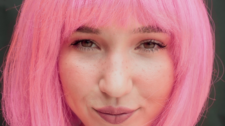 Close-up of a woman with pink hair looking at the camera. Childish and naive look. Dark background. High quality Royalty-Free Stock Footage #1058553010