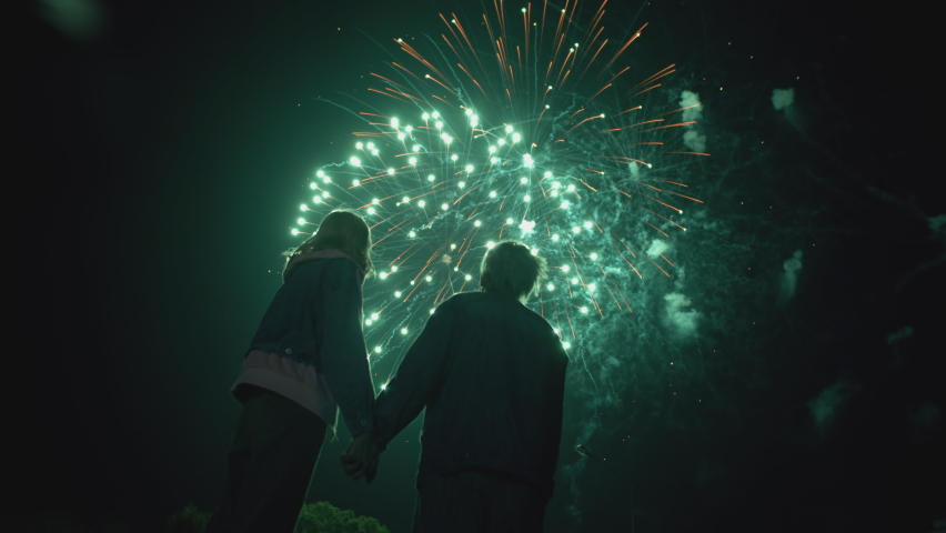 Young Couple Watching Beautiful Fireworks. Silhouette of people watching explosive and colorful fireworks in the evening sky. Holiday event and celebration. In slow motion Royalty-Free Stock Footage #1058561242