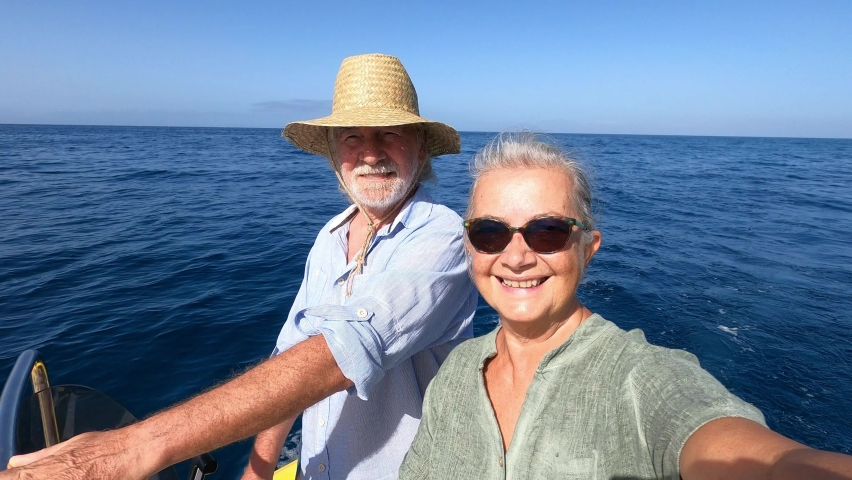 Couple of cute mature people or senior enjoying and having fun together in the middle of the sea or ocean with a small boat or dinghy - woman pensioner taking a selfie with her old man driving the boa