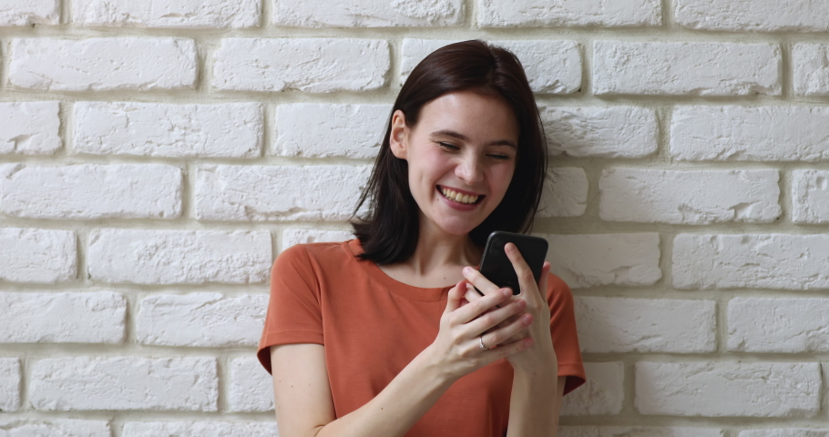 Girl pose against white brick wall hold smart phone read great news feels happy jumps scream with joy. Lottery win, student got scholarship. Invitation and special offer receive, sale discount concept Royalty-Free Stock Footage #1058571259