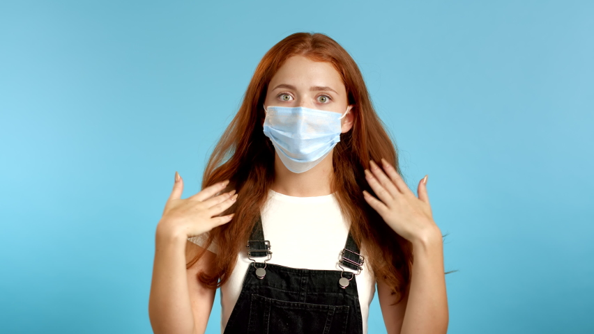 Young tired woman in protective mask is dissatisfied, unhappy.  she exhales from heat or stuffiness, waves arms at herself. Heatstroke concept. | Shutterstock HD Video #1058572255