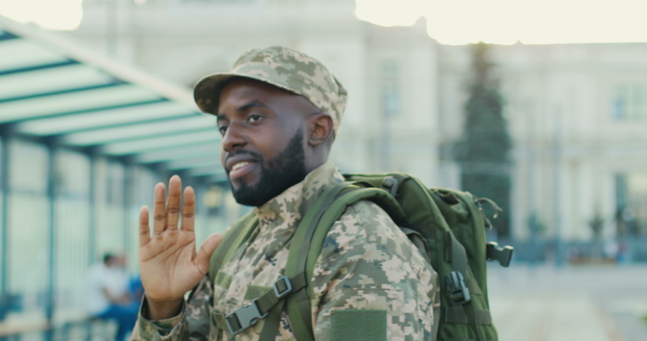 African American young handsome man soldier in military uniform and cap saying goodbye and blowing kisses to girlfriend. Male going to army. Outdoor. Guy and girl farewell. | Shutterstock HD Video #1058573857