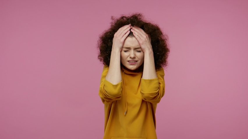Headache. Tired depressed upset young woman afro hairstyle in hoodie feeling unhealthy, suffering unbearable migraine and tension, meningitis, flu symptom. indoor  isolated on pink background | Shutterstock HD Video #1058576410