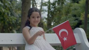 Small girl smiles to the camera in the park and waving the flag of Turkey.Slow motion video.