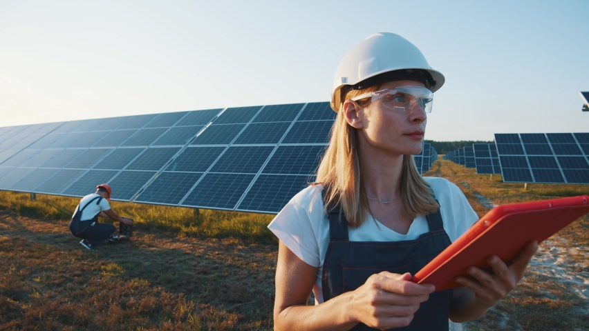 Female ecological engineer uses digital tablet and collects efficient information about solar panels. Photovoltaic solar farm. Green energy. Environment. Royalty-Free Stock Footage #1058579989
