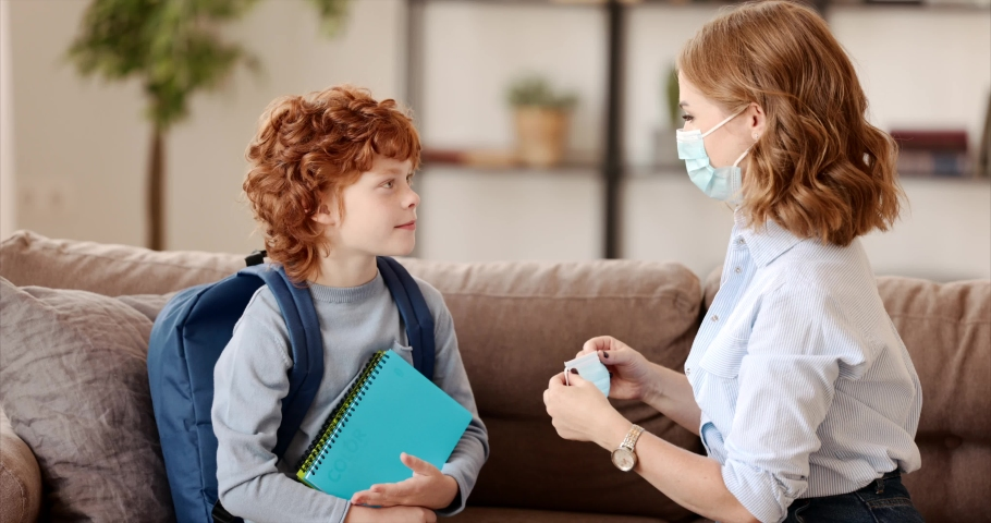 Concept of preventing a coronavirus covid-19 and viral infections. Mother puts on medical mask for little son schoolboy before leaving home for school