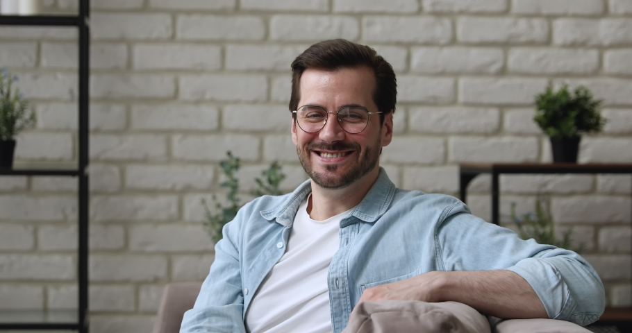 Handsome millennial 30s guy in glasses casual clothes smiling looking at camera sit relaxed on couch at home. Happy homeowner, portrait of attractive man participant of video conference event concept   Shutterstock HD Video #1058581222