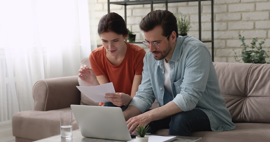 Couple sit on couch holding paper documents discuss loan agreement details term and conditions use e-bank app on computer. Pay utility domestic bills on-line easy remote payment, modern tech concept Royalty-Free Stock Footage #1058581459