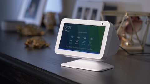 Asking a smart home assistant to show on its display the weather forecast. Smart speaker closeup MONTREAL CANADA AUGUST 2020