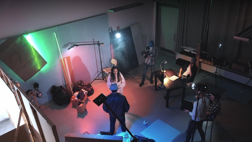 Bird's-eye shot of film shooting in a big film studio. Film crew working on movie production. Producer assistant gives action with movie clapper board and the film crew starting working.