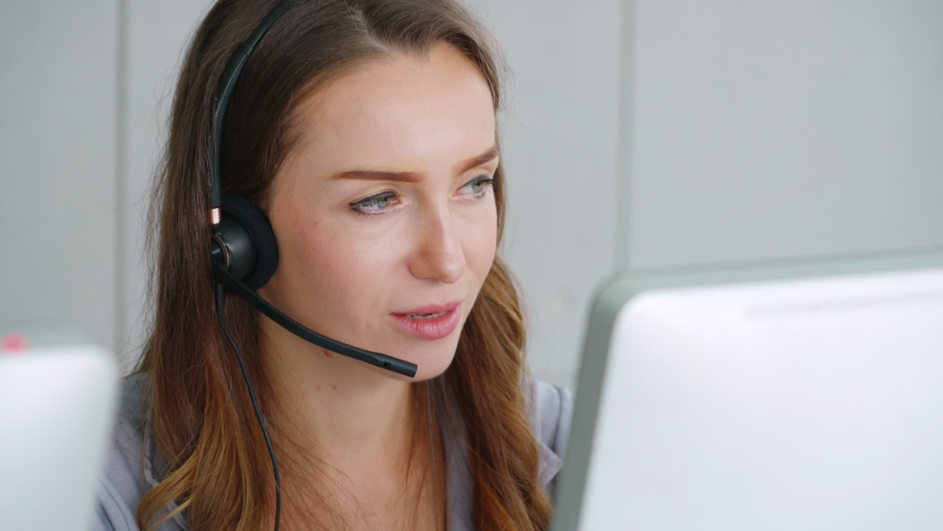Business people wearing headset working in office to support remote customer or colleague. Call center, telemarketing, customer support agent provide service on telephone video conference call. Royalty-Free Stock Footage #1058586130