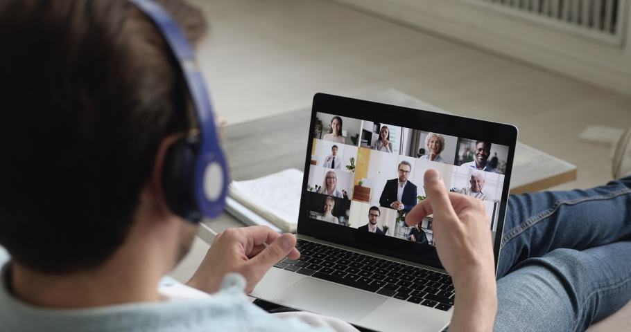 Pc screen where diverse people take part at group video conference, view over male shoulder participant of video call. Telework easy and convenient, modern tech, work from home due quarantine concept
