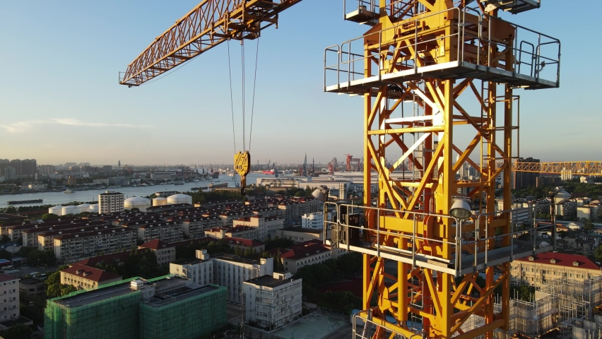 Drone point of view moving up around crane tower in construction site sunset. Close up view of the crane tower lifting material in building site. Industry construction concept footage Shanghai China Royalty-Free Stock Footage #1058589889