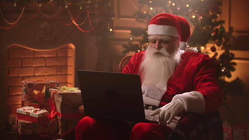 Modern Santa Claus. Cheerful Santa Claus working on laptop and smiling while sitting at his chair with fireplace and Christmas Tree in the background. | Shutterstock HD Video #1058591650