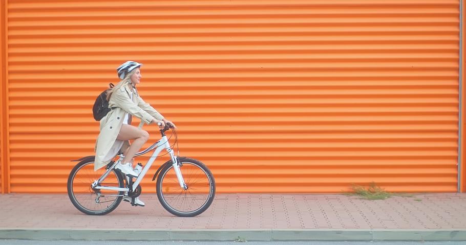 Woman bicyclist in helmet riding on orange background in the city on sport retro bike. 4K video.    Shutterstock HD Video #1058595892