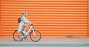 Woman bicyclist in helmet riding on orange background in the city on sport retro bike. 4K video.