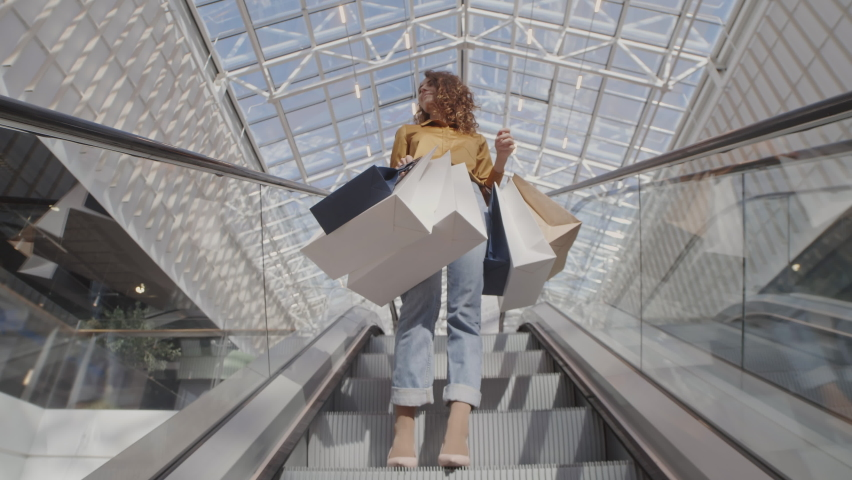 Low angle view of young Caucasian woman wearing trendy clothes standing on escalator with several shopping bags in her hands Royalty-Free Stock Footage #1058601952