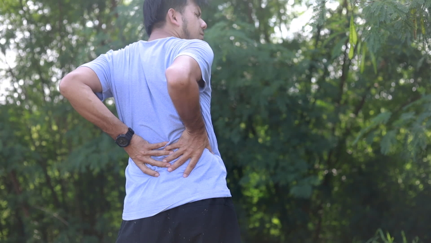Young Asian runner sustains a back pain injury, Sports injury, Man with back pain Royalty-Free Stock Footage #1058602048