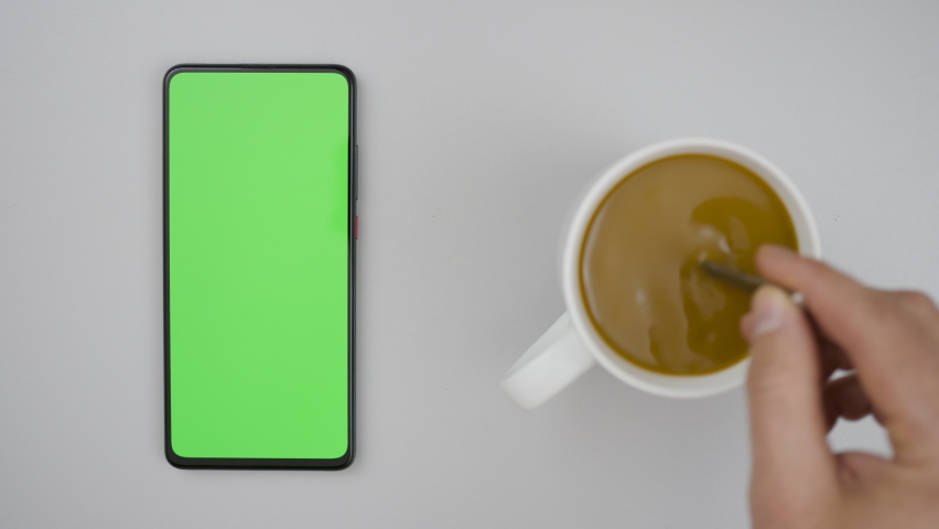 Man Hand Cup of Hot Coffee and Using Smartphone Watching Green Screen Top View. Smartphone with Green Mock-up Screen Business Concept. Person Hand Stirring Coffee with Spoon on Table. | Shutterstock HD Video #1058602387