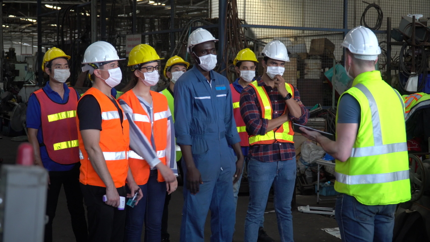 group of factory workers wear protective face mask meeting in industrial factory protect for pollution and coronavirus pandemic or covid 19 outbreak  Royalty-Free Stock Footage #1058602813