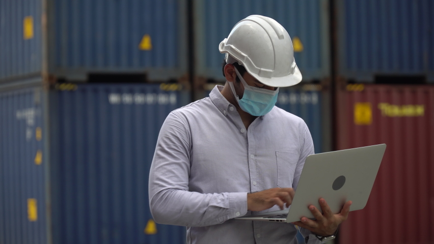 Foreman wareing face mask holding laptop computer talking on the walkie-talkie control loading Containers box at warehouse logistic in Cargo . during coronavirus pandemic or covid 19 outbreak