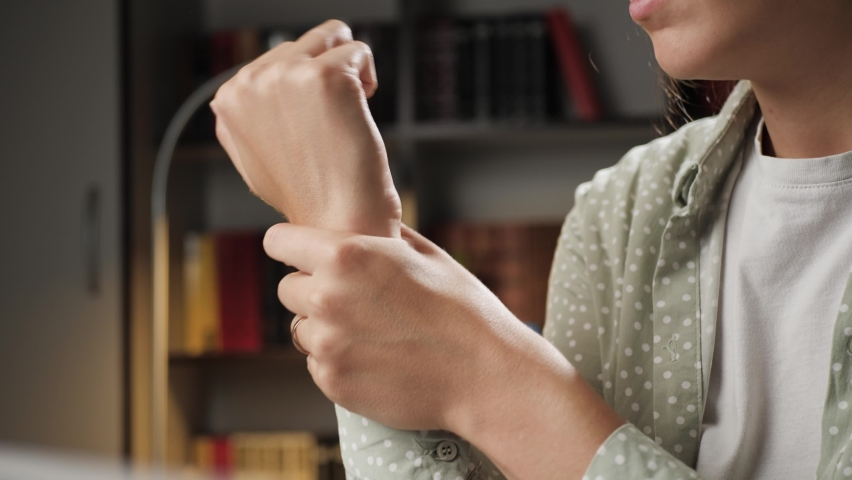 Pain in wrist. Female hand touches wrist and tries to stretch joint. Tendinitis, synovitis, osteoarthritis, sprain, rheumatoid arthritis concept. Close-up