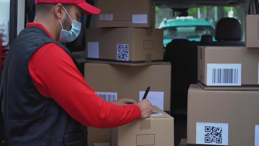 Young courier man writing on tablet informations about delivery packages while wearing face mask for coronavirus prevention - 4K video | Shutterstock HD Video #1058610988