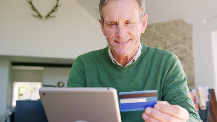 Senior man at home buying products or services online using digital tablet and credit card - shot in slow motion