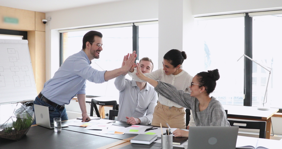 Motivated multicultural happy business people give high five at office meeting. African, caucasian and indian employees team celebrate leadership, professional success, good teamwork strategy concept. Royalty-Free Stock Footage #1058617060