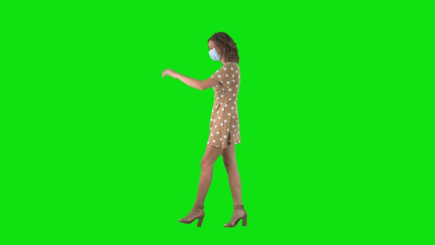 Young walking woman with face mask greeting with elbow bump for corona virus prevention on chroma key green screen. Social distance concept.  Royalty-Free Stock Footage #1058618611