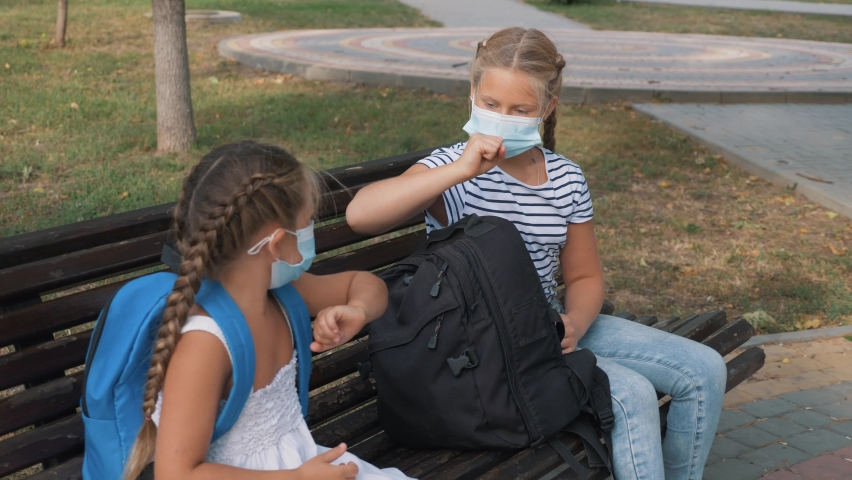 Schoolgirls in medical masks are sitting in the park. Social distancing of schoolgirls with friends and family for the sake of safety in the park. Non-contact elbow farewell. Bump avoid greeting. Royalty-Free Stock Footage #1058619505