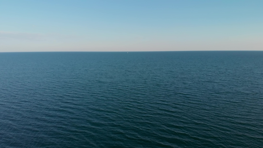 One lonely white yacht sail in the distance on sea horizon high aerial pursuit shot.   Shutterstock HD Video #1058621752
