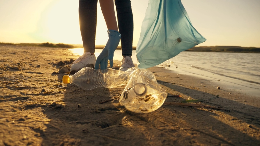 Teamwork cleaning plastic on the beach. Volunteers collect trash in a trash bag. Plastic pollution and environmental problem concept. Voluntary cleaning of nature from plastic. Greening the planet Royalty-Free Stock Footage #1058621932
