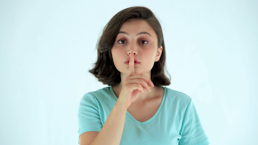 Brunette young woman shushing, asking to keep silence or secrecy. Studio shot, isolated on white background	 | Shutterstock HD Video #1058623747