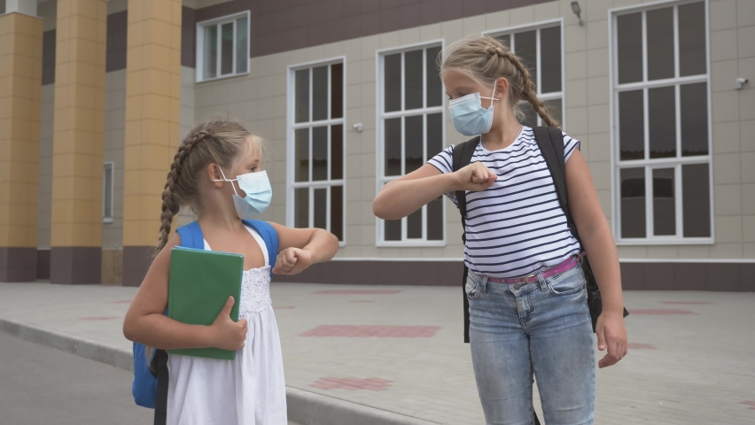 Schoolgirl girls in protective masks. Social distancing of schoolgirls. Non-contact elbow farewell. Bump avoid greeting. Schoolgirl girls communicate in protective masks Royalty-Free Stock Footage #1058624659