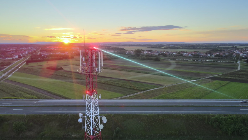 Antenna of communication tower sends signals to self-driving car on a highway at the edge of agricultural fields. Digital wireless connection to a self-driving smart car with automatic sensor driving. | Shutterstock HD Video #1058627710