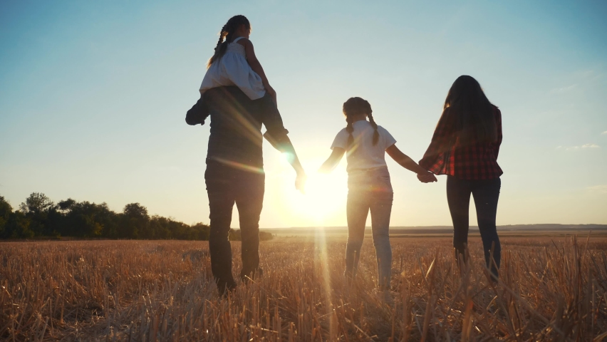 people in the park. happy family silhouette walk at sunset. mom dad and daughters walk holding hands in the park. happy family kid dream concept. parents and fun children walking back silhouette Royalty-Free Stock Footage #1058628376