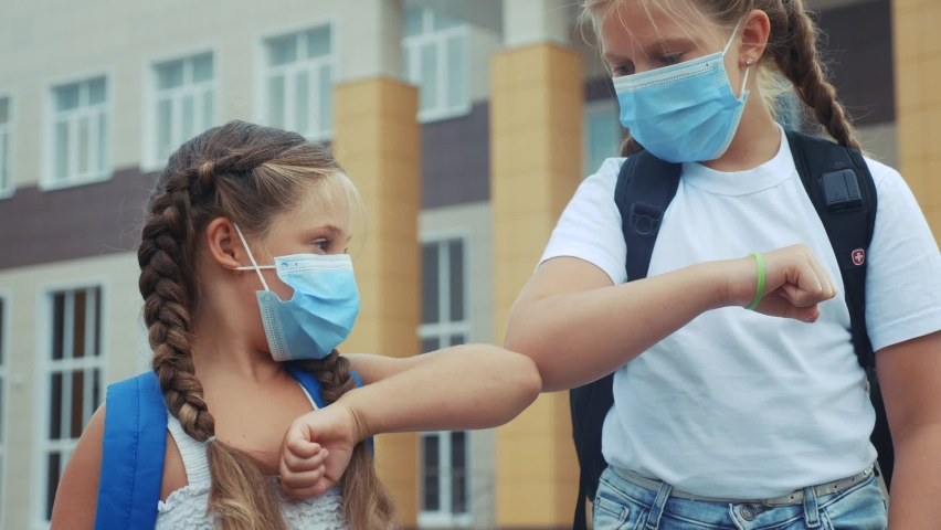children kids in masks making elbow greetings without shaking hands bump avoid greeting. during the coronavirus period social distance. bump avoid greeting  Royalty-Free Stock Footage #1058628394