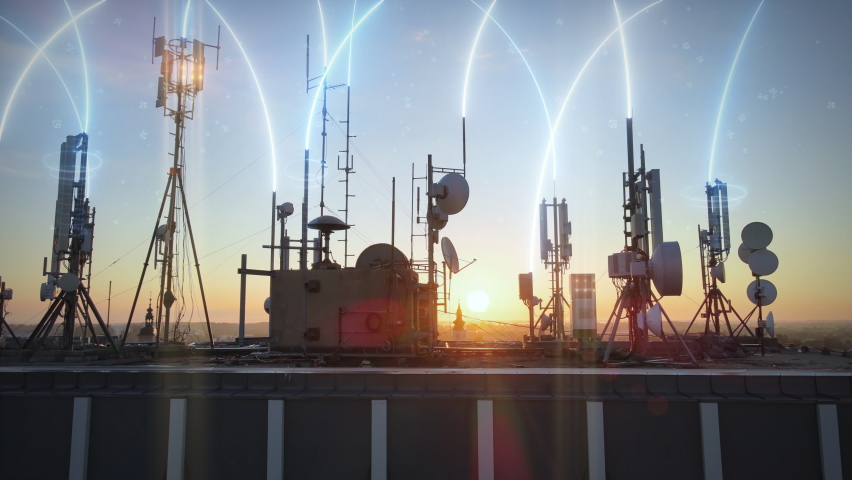 5G rooftop base station covered with telecom tower antenna with graphics effect of microwave radiation and pollution. Aerial slide shot during sunset. Urban futuristic cityscape | Shutterstock HD Video #1058630941