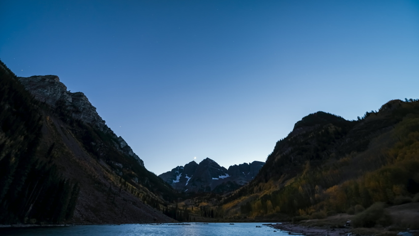 Timelapse time lapse of Maroon Bells lake view of milky way, moon in dark sky in Aspen, Colorado USA at night with Rocky Mountain peak in October autumn