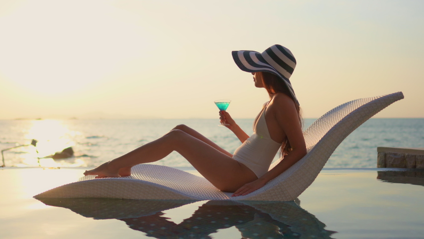 Pretty woman in white bathing suit and wide hat reclining in modern chair in swimming pool overlooking a beach at sunset. Lady with colorful tropical drink crosses legs watching ocean.