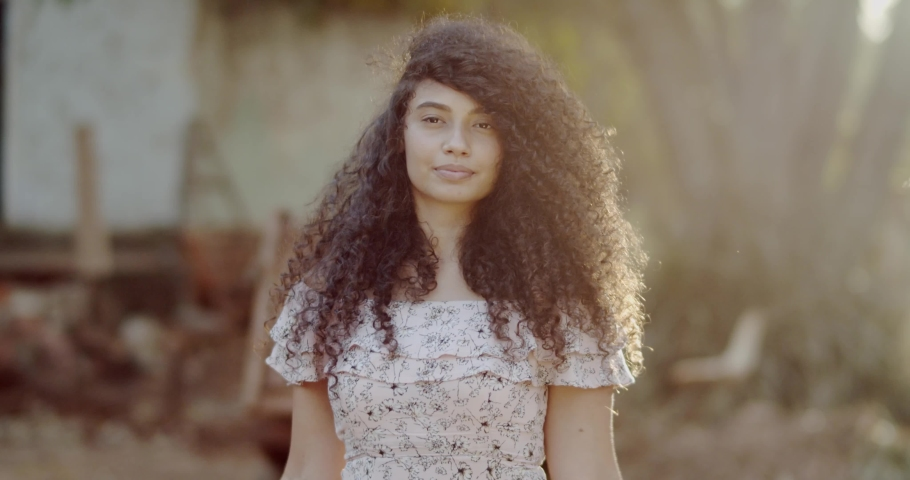 Young curly hair woman covering with lgbt pride flag. Alone. One. Keeping fist up, covering LGBT flag. LGBT+ flag on outdoor background. 4K. | Shutterstock HD Video #1058635312