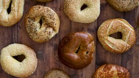 Grabbing a Bagel from a Variety of Bagels on a Wooden Table