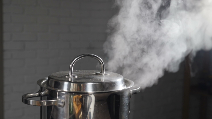 Steam or Vapour clouds rising from boiling water in saucepan on stove. Steam from pan while cooking. Cooking process in slow motion. Steam and white smoke rising on dark background. Full hd Royalty-Free Stock Footage #1058638984