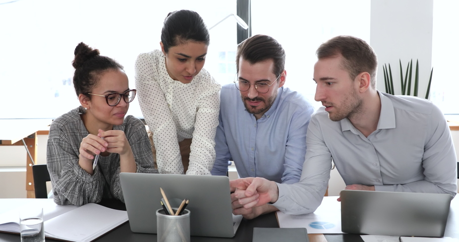 Multi ethnic colleagues staff members gather in modern office boardroom using computer discussing common project, make analysis of work done sales statistics and forecasting. Teamwork activity concept Royalty-Free Stock Footage #1058642047