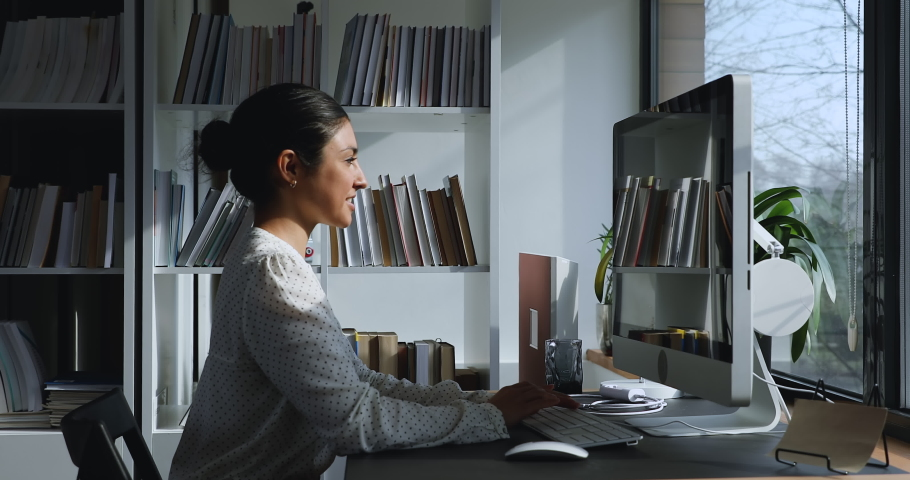 Pretty Indian ethnicity 30s confident businesswoman sit in office workplace work on computer do job feels satisfied, side view. Modern technologies, new application, successful comfort workday concept Royalty-Free Stock Footage #1058642113