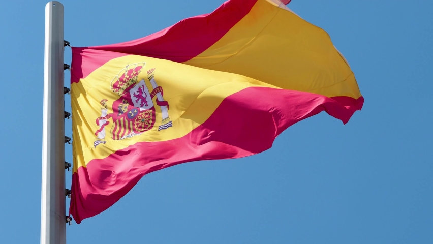 Spanish flag fluttering in the wind. National flag against a blue sky, high flagpole #1058646067